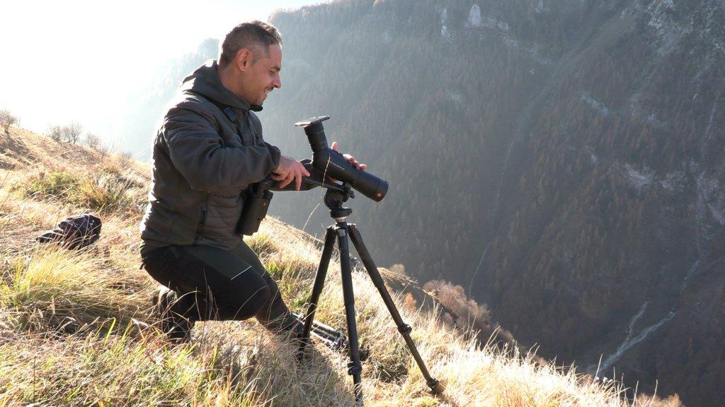 Bobo Audino intento a filmare il camoscio che appare nel video con il suo Smartphone accoppiato al Leica Apo Televid di Leica, tenuto a ingrandimento 50x
