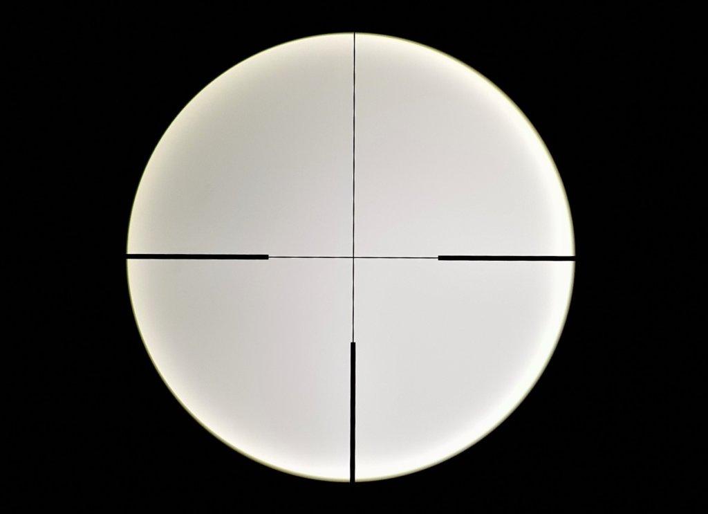 Il reticolo 4a dell'Amplus fotografato attraverso il cannocchiale con uno smartphone. Quando è spento, il puntino centrale non si vede.
